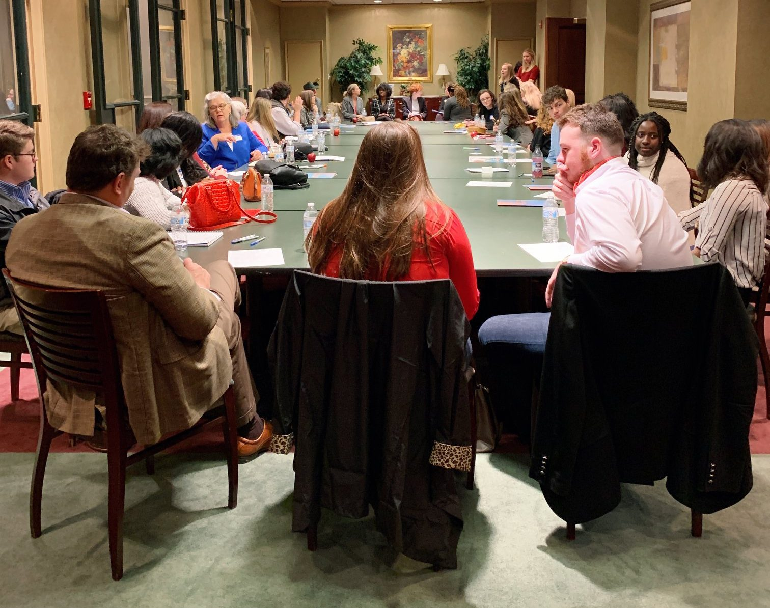 Interns sit around a large table discussing issues.