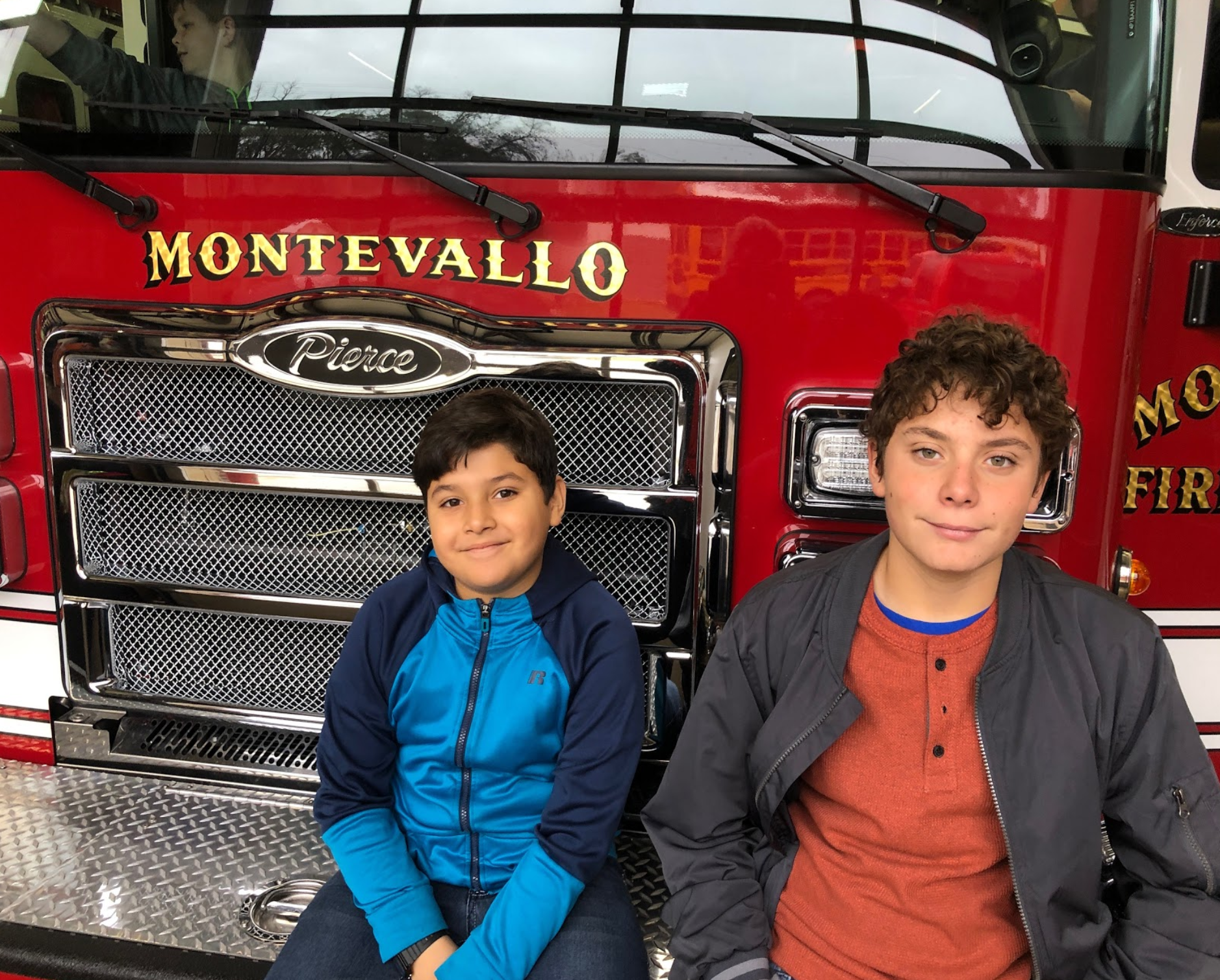 Children sitting next to fire engine.